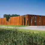 Einschnitte in der Cortenstahlhülle verleihen der Fassade das Aussehen von Baumrinde.