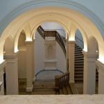 Im zentralen Treppenhaus sorgt indirektes Licht für blendfreie Helligkeit und Betonung des Deckengewölbes.