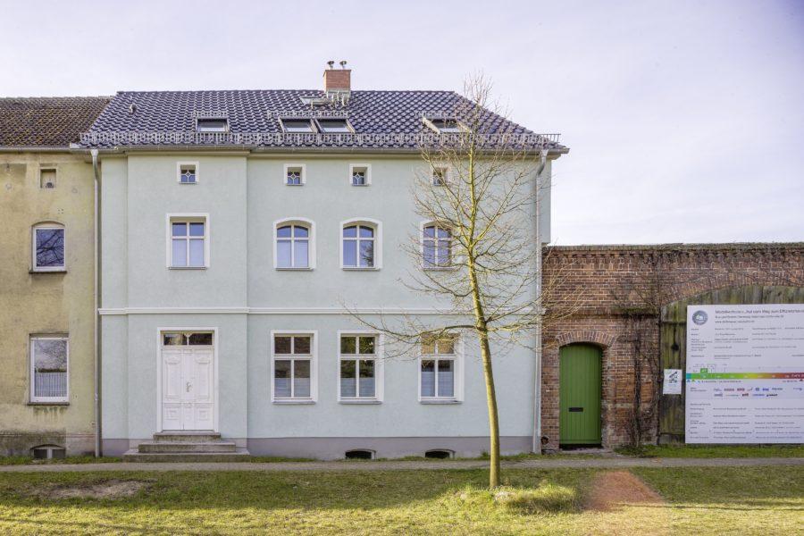 Ein renoviertes Haus mit mintgrüner Fassade zwischen Altbestand.