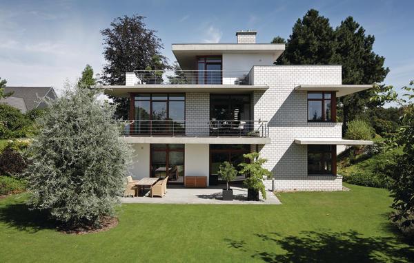 Dreigeschossiges Haus mit hellem Sichtmauerwerk. Großflächige Balkone und Fensterüberhänge geben dem Haus einen terrassenartigen Aufbau.