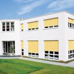 Der Sonnenschutz in der Fensterlaibung statt auf der Fassade ordnet sich dem kubischen Charakter des Baukörpers unter und betont die halbrunde Eingangssituation. Bild: Reflexa