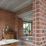 Wohn- und Esszimmer mit unververkleideten Ziegelwänden und Sichtbetondecke.