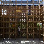 Sieben Meter hohe Bambusregale säumen im Haus die Fassaden und schmiegen sich wie eine hölzerne Matrix an die Ziegelwände.