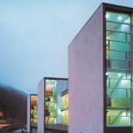 Quer angeordnete Riegel stehen parallel zur Bundesstraße, miteinander verbunden durch Glasbauten.