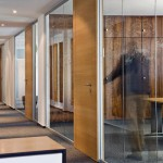 Büros im OG sind zum Flur hin mit Glastrennwänden transparent geschlossen, ergänzt von Türen in Eiche.