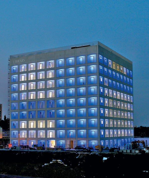 Die neue Stadtbibliothek leuchtet in der Nacht blau über das noch unbebaute Areal.