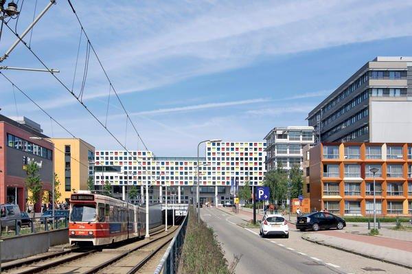 Städtebauliche Aufwertung einer viel befahrenen Straßenkreuzung mit Bahndurchgang durch den Schul-Neubau.