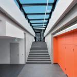 Helle Sichtbetonflächen bilden vor den Klassenzimmern einen klaren Hintergrund, kontrastiert von farbigen Zugängen.-