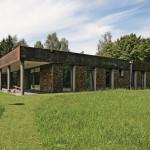 Elegant und zurückhaltend fügt sich dieser Bungalow mit der Natursteinfassade Stonepanel und Attikablenden aus Cortenstahl in die Landschaft.