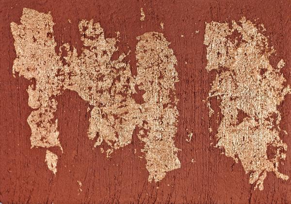 Blattmetall wird mit Tapetenkleister auf vorab grob strukturiertem Lehmputz, Farbe Feuer, aufgebracht. Anschließend werden die Blattmetallreste mit feinem Besen abgekehrt.