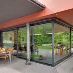 Hebe-Schiebetüranlage als transparente Trennung zwischen Küche und überdachtem Terrassenbereich.