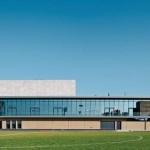 Vom tiefer gelegenen Spielfeld wird die Dimension des Neubaus deutlich. Der lange Glasriegel beherbergt Nebenräume und Restaurant. Bild: Felix Krummlauf