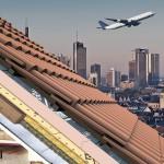 Ein abhebendes Flugzeug vor der Kulisse der Frankfurter Innenstadt, davor ein Schnitt durch ein ziegelgedecktes Dach mit darunterliegendem Wohnzimmer. Bilder: Klöber