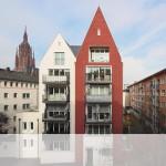 Straßenansicht mit Balkonseite: Neubau von zwölf Wohnungen hinter der Fassade von zwei hohen, schmalen Giebelhäusern.