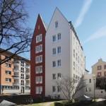 Von der halböffentlichen Hof- und Grünanlage gesehen: Rot-weiße Giebelhaus-Architektur in traditionell-moderner Formensprache.