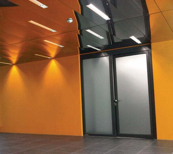 Milchglastüre in orangefarbener Wand. Bild: Lindner Group
