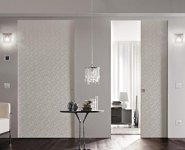 Zwei Schiebetüren mit weißer Reliefstruktur ergänzen das elegante Raumabiente. Bild: Eclisse
