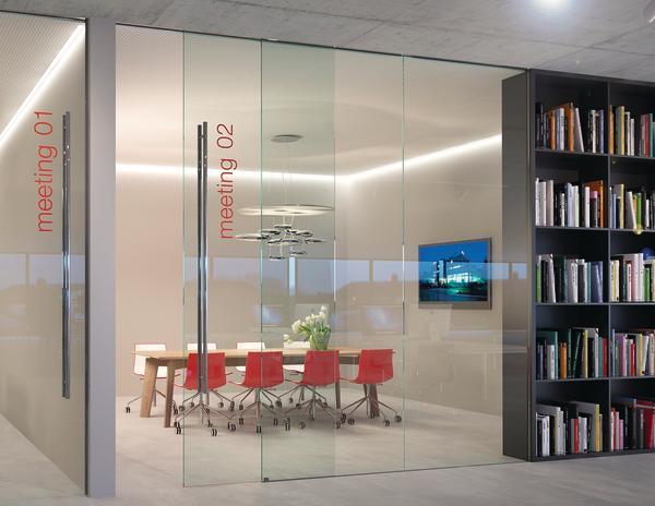 Stockwerkshohe Glastrennwand mit Glasschiebetür, komplett ohne Rahmen. Bild: Hawa AG Schiebebeschlagsysteme