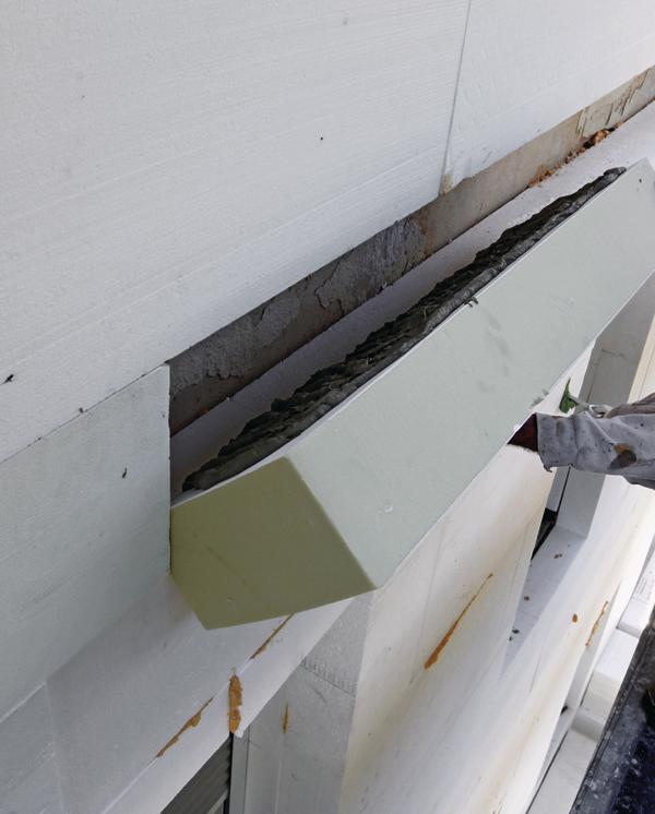 Eine Dämmplatte wird an einer Außenwand angebracht. Bild: puren