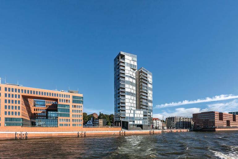 Zum Schutz vor Hafenlärm und Wetter wurden die Außensitze eines Hamburger Wohnhochhauses mit einer rahmenlosen Balkonverglasung ausgestattet.