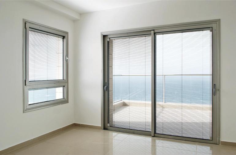 Terrassenschiebetür aus Glas mit halbtransparenten Sonnenschutzrollos. Bild: Glas Trösch / Sanco Beratung