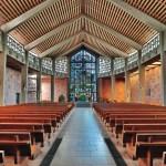 Kirchenraum der schlichten, dreischiffigen Basilika mit sichtbar verbauten Werkstoffen.