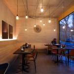 Café als zentraler Treffpunkt für Nutzer des Hauses und Besucher von außen. Beton und Holz ergänzen sich optisch wie raumakustisch.