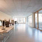 Im Innern optimieren filigrane Holz-Akustikpaneele die Raumakustik des puristischen Stahlbeton-Skelettbaus.