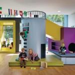 Die farbigen Rahmenelemente sind Teil des Gebäudes, Möbelstück und Spielgerät zugleich.
