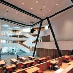 Ans zentrale Foyer mit seinen expressiv gestalteten Treppen grenzt unmittelbar das multifunktionale Auditorium an. Bild: Christian Richters