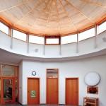 Der bis zum Dach offene Innenraum ist geprägt durch eine Lichtkuppel mit Holzbinderdachstuhl und Festverglasungen in der Kombination Aluminium-Holz.