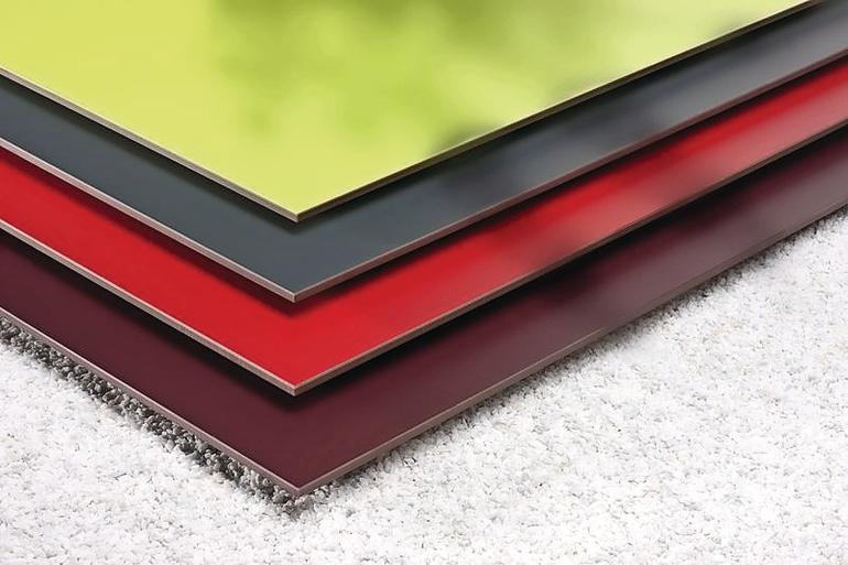 Vier farbige Metallplatten auf einem weißen Teppich. Bild: FunderMax