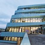 Zaha Hadid-Architektur: Fassade aus geschwungenem Glas nimmt den Kurvenverlauf der Straße auf. Bild: Katrin Heyer für Regiolux