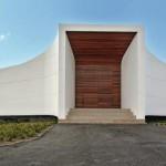 Klare Materialkontraste zwischen weißem Mineralwerkstoff und rötlichen Holzflächen, die den Eingang bilden.