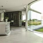 Der von wenigen schlanken Stützen getragene Wohnbereich wird vor allem durch die geschwungene Glasfront zum Wasser bestimmt.