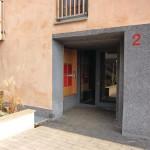 Der Sockelputz ist rund um den Eingang und die Fensterflächen des Cafés bis auf Geschosshöhe ausgeführt.