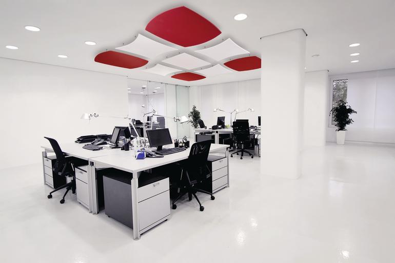 Der durchgängig weiße Büroraum mit glattem Boden wird durch akustisch wirksame, rote Deckensegel aufgelockert und ein wenig gemütlicher gestaltet. Bild: Owa
