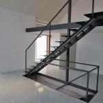 Über die Stahltreppe – mehr Möbelstück als Bauteil – werden vom EG aus das Untergeschoss sowie die darüberliegende Arbeits-Galerie erschlossen. Bild: Till Schaller