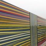 Wie bunte Wollfäden wirkt der Farbverlauf an der Fassade – als Reminiszenz an die Herkunft des Gebäudes. Bilder: Metawell