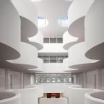 Die Oberlichter beleuchten sowohl die Emporen mit den apsidenförmigen Balkonen als auch den multifunktionalen Eingangsraum im EG.