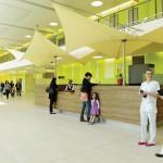 Eingangshalle als Zentrum der Magistrale mit großflächigen Verglasungen zum Außenbereich und mit raumprägender Farbwand. Bild: Svenja Bockhop, Berlin