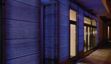 Die Fassade aus massivem Betonwerkstein wird bei Dunkelheit zur Spielfläche farbdynamischen Lichts.