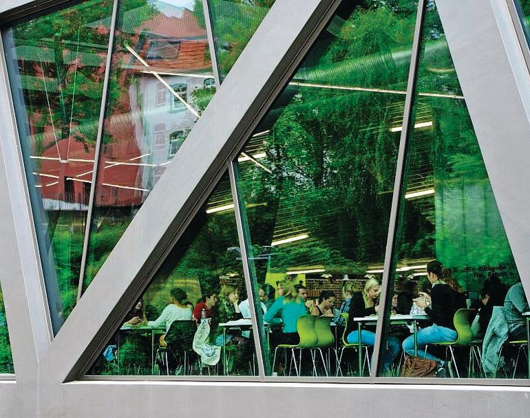 Große Fenster lassen den Blick in den Speisesaal der Mensa zu. Bild: paulus.photography (Unimensa, Kassel | Architekt: augustinundfrankarchitekten)