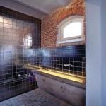 Ehemalige Pferdetröge sind in das moderne Badkonzept eingebunden.