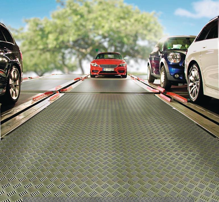 Autos auf Plattformen eines automatischen Parksystems, Naturbild im Hintergrund. Bild: Sateg