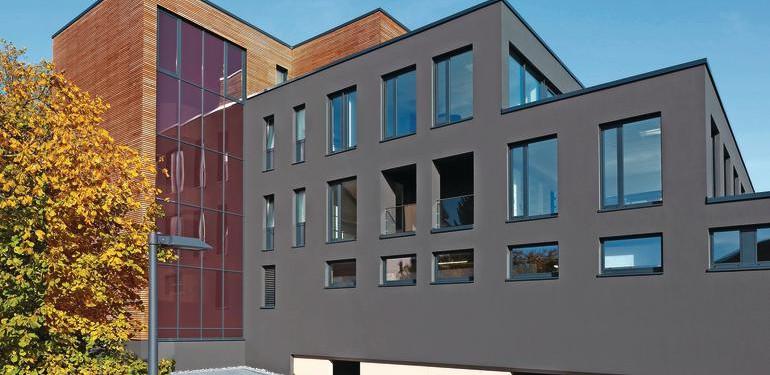 Gestaltung mit Holz, Glas und dunklem Putz  hier mit einer Acryl-Fassadenfarbe in TSR-Formulierung. Bild: Brillux