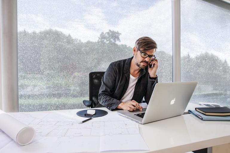 Mann arbeitet an seinem Laptop vor einer sehr schmutzigen Fensterfront. Bild: Sattler AG