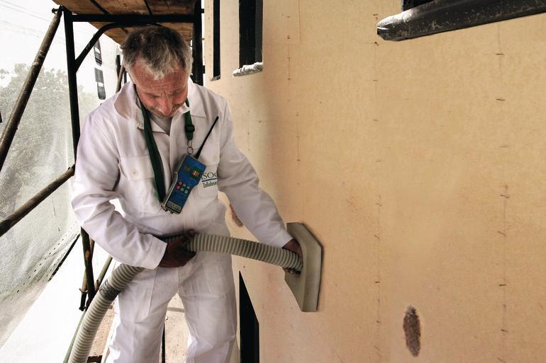 Die Dämmschicht wird von einem Arbeiter über einen Schlauch in die Wand eingebracht. Bild: Inthermo