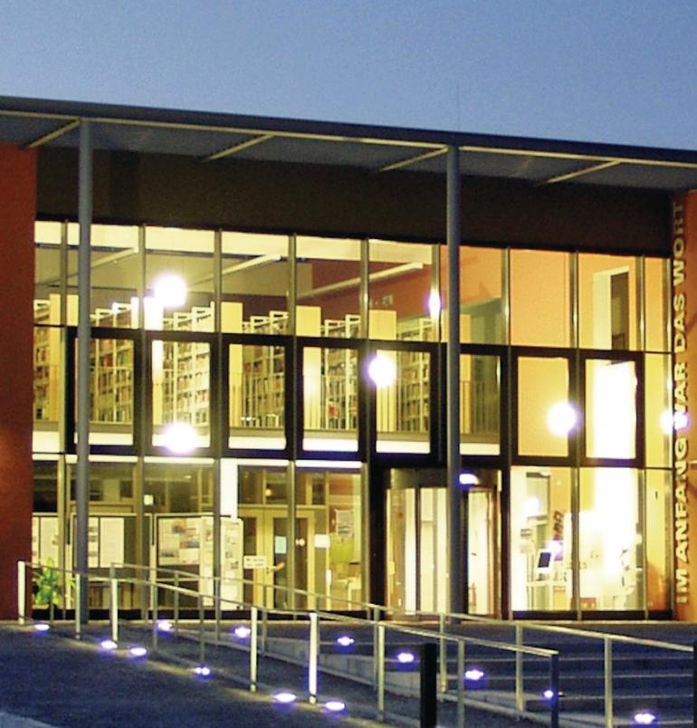Hell erleuchtete Fensterfront einer Bibliothek. Bild: Kneer-Südfenster