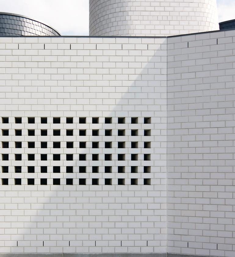 Weiße Ziegelfassade mit Gittermuster zum Luft- und Lichteinlass. Bild: Witte